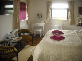 Fuschia Suite bedroom and ensuite slipper bath at Clouds B&B, Stoke, Hartland